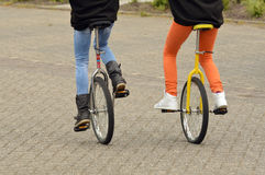 Equilibration. Balancing girls driving unicycles outdoors Royalty Free Stock Images