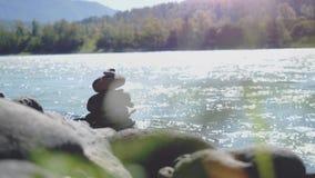 Equilibre a pedra na costa do rio na paisagem da natureza na república de Altai, o fluxo da água em um movimento lento 4k, 3840x2 filme
