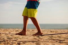 Equilibrio adolescente en slackline con la opinión del mar Foto de archivo libre de regalías