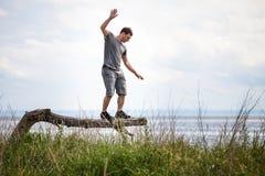 Equilibrio adulto joven en un árbol en vacaciones Fotos de archivo libres de regalías