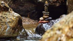 Equilibrio di pietra del movimento lento che impila alla riva del fiume ed alla luce solare di mattina archivi video