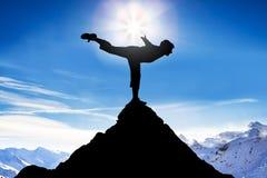 Equilibrio practicante del hombre en un pico de una montaña Foto de archivo libre de regalías