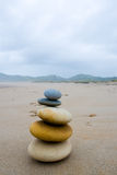 Equilibrium. Five stones accumulated in balance on the sand of a beach Royalty Free Stock Photo