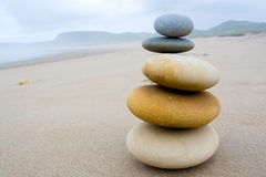 Equilibrium. Five stones accumulated in balance on the sand of a beach Royalty Free Stock Photos