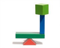 Equilibrium. Demonstrated by colourful wooden toy blocks balanced on a horizontal crossbar on a triangular pivot in perfect balance, over white Royalty Free Stock Image