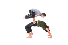 Equilibrium. Flexible two men doing warmup equilibrium  exercise - isolated on white Royalty Free Stock Photos