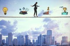 Equilibrium and leadership concept. Side view of young businesswoman balancing on tightrope with business sketch on city background. Equilibrium and leadership stock images
