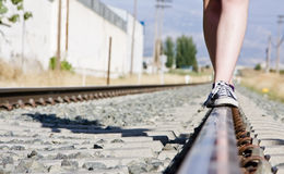 Equilibrium over railtrack. Woman walking in equilibrium over rail track Royalty Free Stock Photo
