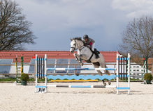 Equine competition. Man on white horse above hurdle Stock Photo