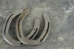 Equine them with old, worn horseshoes on a scratched and damaged steel background. Lots of texture with copy space. Good for any equestrian theme including stock image