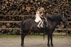 Equine therapy, recreation concept. Children sit in rider saddle on animal back. Friend, companion, friendship. Sport, activity, entertainment. Girls ride on royalty free stock photos