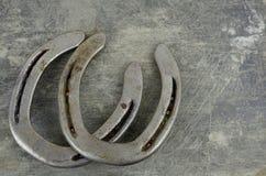 Equino ellos con las herraduras viejas, gastadas en un fondo de acero rasguñado y dañado Porciones de textura con el espacio de l imagen de archivo