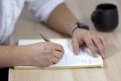 Equipa as mãos no equipamento branco escreve com a pena do rolo no papel na tabela de madeira algum latino, ou os termos da medic fotografia de stock