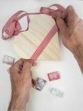 Equipa as mãos que amarram a fita em uma caixa de presente dada forma coração e com tur Imagens de Stock Royalty Free