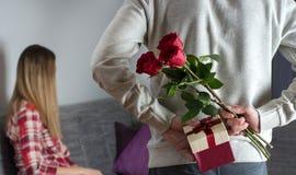 Equipa as mãos que escondem guardando o ramalhete chique de rosas vermelhas e o presente com a fita branca atrás da parte traseir foto de stock