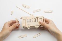 Equipa as mãos que montam o brinquedo de madeira do ônibus bonde Fotografia de Stock