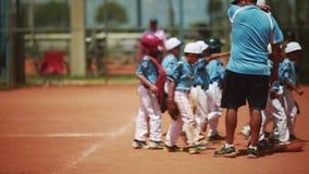 A equipa de beisebol da criança com treinadores mesmo antes de um jogo filme