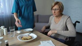 Equipa de tratamento médica que traz a placa de sobremesa à senhora doente na cadeira de rodas, auxílio filme