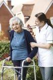 Equipa de tratamento que ajuda a mulher superior a andar no jardim usando o quadro de passeio foto de stock