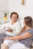 Equipa de tratamento que come um copo do chá com uma mulher idosa Fotografia de Stock Royalty Free