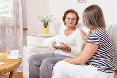 Equipa de tratamento que come um copo do chá com uma mulher idosa Foto de Stock