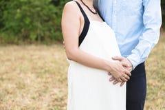 Equipa e o braço das mulheres que encontra-se no estômago da mulher gravida foto de stock royalty free