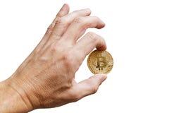 A equipa a mão que mantém um bitcoin isolado no branco Foto de Stock