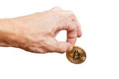 A equipa a mão que mantém um bitcoin isolado no branco Fotografia de Stock