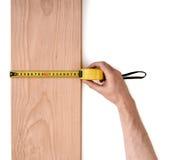 Equipa a mão que mede a prancha de madeira com uma linha da fita isolada no fundo branco fotografia de stock