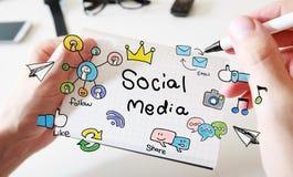 Equipa a mão que tira o conceito social dos meios no caderno Foto de Stock