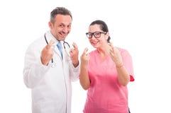 A equipa médica alegre indica o sinal da boa sorte imagens de stock
