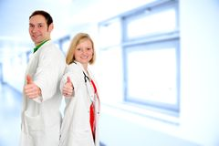 Equipa médica amigável no revestimento do laboratório com polegares acima Imagem de Stock Royalty Free