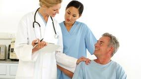 Equipa médica amigável que fala com paciente deficiente vídeos de arquivo
