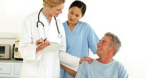 Equipa médica amigável que fala com paciente deficiente video estoque