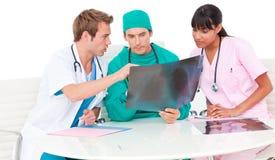 Equipa médica bem sucedida que olha o raio X foto de stock