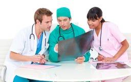 Equipa médica concentrada que olha o raio X fotos de stock