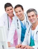 Equipa médica de sorriso que trabalha em um computador imagem de stock