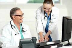 Equipa médica de sorriso que trabalha no computador foto de stock