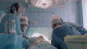 Equipa médica do hospital que veste a roupa cirúrgica que executa a cirurgia usando o equipamento esterilizado video estoque