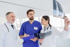 Equipa médica profissional que discute a imagem do roentgen imagens de stock royalty free