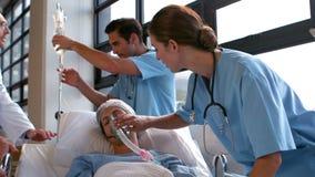 Equipa médica que carreg um paciente à unidade de cuidados intensivos video estoque
