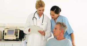 Equipa médica que fala com paciente deficiente filme