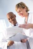 Equipa médica que revê a carta imagem de stock royalty free