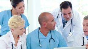 Equipa médica que trabalha junto durante a reunião video estoque