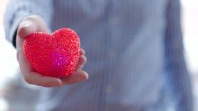 Equipa a mão que dá afastado seu coração video estoque