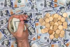 Equipaggi afferrare un batuffolo delle banconote in dollari sopra denaro contante Fotografia Stock