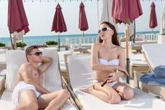 Equipaggi ammirare la sua donna mentre si rilassano sulle chaise-lounge fotografia stock