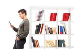 Equipaggi appoggiarsi uno scaffale per libri e la battitura a macchina sul suo telefono Immagine Stock