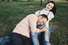 Equipaggi ascoltare la pancia incinta del ` s della moglie e sorridere fotografia stock libera da diritti