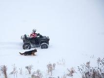 Equipaggi ATV di guida nell'inverno con il cane Immagine Stock Libera da Diritti